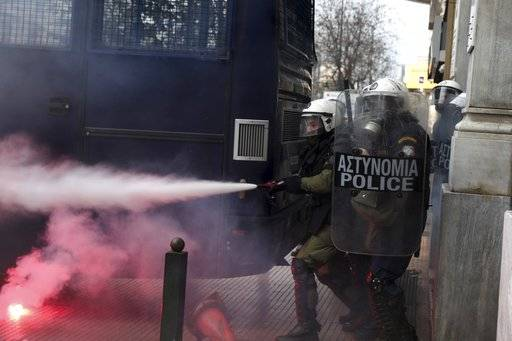 CORRECT NAME OF THE PHOTOGRAPHER Riot policemen spray tear gas during a scuffle on the sidelines of a rally in Athens, Sunday, Feb. 4, 2018. Protesters from across Greece converged Sunday on Athens' main square outside parliament to protest a potential Greek compromise in a dispute with neighboring Macedonia over the former Yugoslav republic's official name.