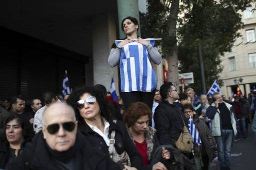 A woman holds the Greek flag as she gathers with other protesters in a rally in Athens, Sunday, Feb. 4, 2018. Protesters from across Greece converged Sunday on Athens' main square outside parliament to protest a potential Greek compromise in a dispute with neighboring Macedonia over the former Yugoslav republic's official name.