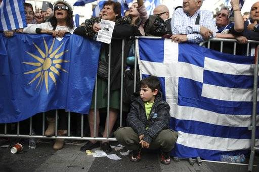 Protesters shout slogans as a boy sits between the Greek flag, right, and the star of Vergina the emblem of the ancient Greek kingdom of Macedonia during a rally in Athens, Sunday, Feb. 4, 2018. Protesters from across Greece converged Sunday on Athens' main square outside parliament to protest a potential Greek compromise in a dispute with neighboring Macedonia over the former Yugoslav republic's official name.