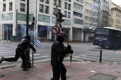 Protesters throw items at riot policemen during a scuffle on the sidelines of a rally in Athens, Sunday, Feb. 4, 2018. Protesters from across Greece converged Sunday on Athens' main square outside parliament to protest a potential Greek compromise in a dispute with neighboring Macedonia over the former Yugoslav republic's official name.