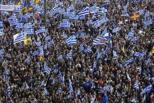 People with Greek flags attend a rally in Athens, Sunday, Feb. 4, 2018. Protesters from across Greece were thronging the Greek capital's main square outside parliament Sunday to protest a potential Greek compromise in a dispute with neighboring Macedonia over the former Yugoslav republic's official name.