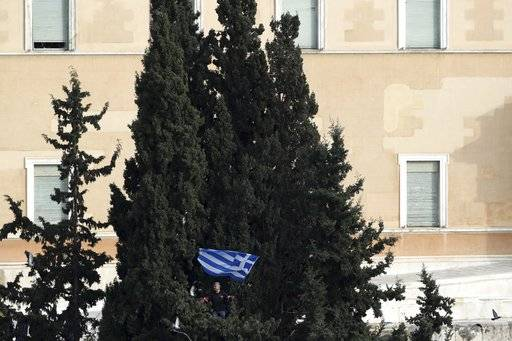 A protester waves a Greek flag from inside a tree he has climbed outside parliament during a rally in Athens, Sunday, Feb. 4, 2018. Protesters from across Greece converged Sunday on Athens' main square outside parliament to protest a potential Greek compromise in a dispute with neighboring Macedonia over the former Yugoslav republic's official name.