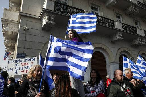 Protesters hold Greek flags during a rally in Athens, Sunday, Feb. 4, 2018. Protesters gather in the Greek capital for a mass rally to protest a potential Greek compromise in a dispute with neighbouring Macedonia over the former Yugoslav republic's official name.