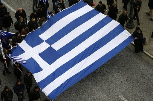 Protesters hold a Greek flag ahead of a rally in central Athens, Sunday, Feb. 4, 2018. Protesters have begun arriving in the Greek capital for what is expected to be a massive rally to protest a potential Greek compromise in a dispute with neighboring Macedonia over the former Yugoslav republic's official name.