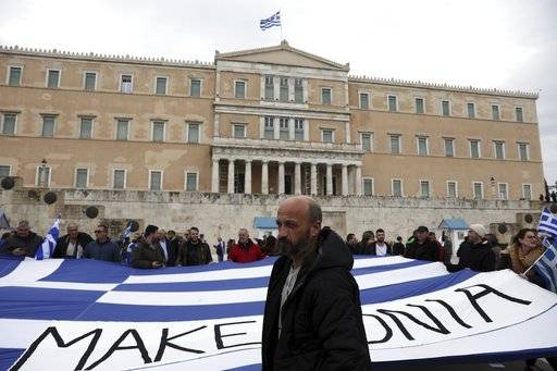 "Protesters hold a Greek flag reads ""Macedonia"" in front of the Greek Parliament during a rally in Athens, Sunday, Feb. 4, 2018. Protesters were arriving in the Greek capital for what is expected to be a massive rally Sunday afternoon to protest a potential Greek compromise in a dispute with neighboring Macedonia over the former Yugoslav republic's official name."
