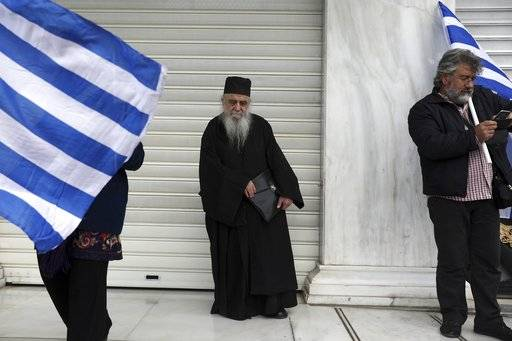 A Greek Orthodox priest stands between protesters holding Greek flags during a rally in Athens, Sunday, Feb. 4, 2018. Protesters were arriving in the Greek capital for what is expected to be a massive rally Sunday afternoon to protest a potential Greek compromise in a dispute with neighboring Macedonia over the former Yugoslav republic's official name.