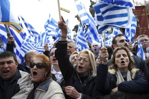 Protesters shout slogans as they hold Greek flags during a rally in Athens, Sunday, Feb. 4, 2018. Protesters were arriving in the Greek capital for what is expected to be a massive rally Sunday afternoon to protest a potential Greek compromise in a dispute with neighboring Macedonia over the former Yugoslav republic's official name.