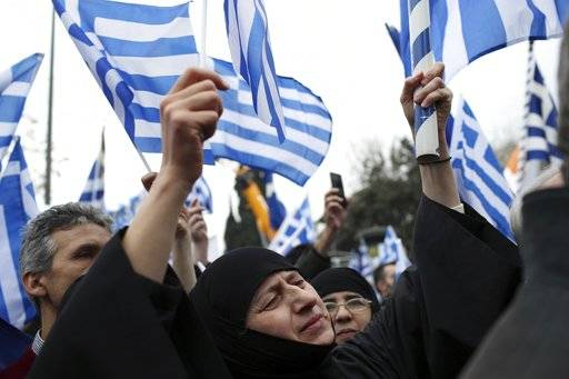 A nun waves a Greek flag during a rally in Athens, Sunday, Feb. 4, 2018. Protesters gather in the Greek capital for a massive rally to protest a potential Greek compromise in a dispute with neighboring Macedonia over the former Yugoslav republic's official name.