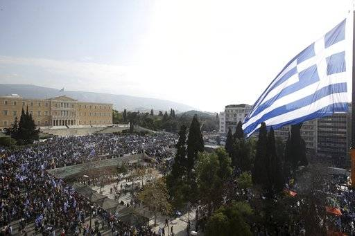 A giant Greek flag hangs from a crane waves over protesters during a rally in Athens, Sunday, Feb. 4, 2018. Protesters gather in the Greek capital for a massive rally to protest a potential Greek compromise in a dispute with neighboring Macedonia over the former Yugoslav republic's official name.
