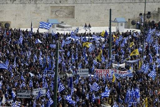 People with Greek flags attend a rally in front of the Tomb of the Unknown Soldier in Athens, Sunday, Feb. 4, 2018. Protesters gather in the Greek capital for a massive rally to protest a potential Greek compromise in a dispute with neighboring Macedonia over the former Yugoslav republic's official name.