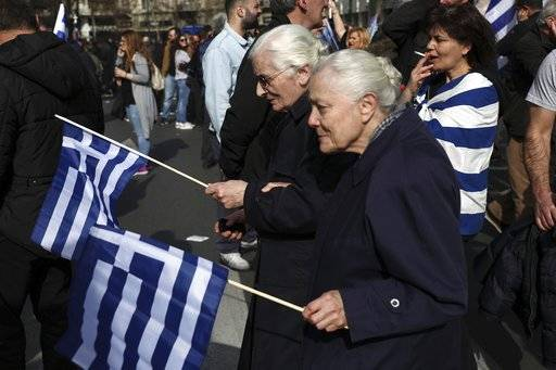 Elderly women with Greek flags attend a rally in Athens, Sunday, Feb. 4, 2018. Protesters gather in the Greek capital for a massive rally to protest a potential Greek compromise in a dispute with neighboring Macedonia over the former Yugoslav republic's official name.