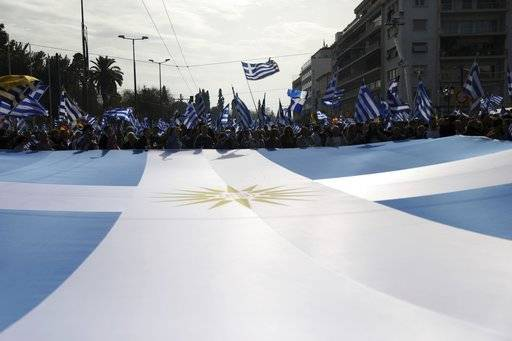 Protesters hold a Greek flag with the star of Vergina the emblem of the ancient Greek kingdom of Macedonia, during a rally in Athens, Sunday, Feb. 4, 2018. Protesters gather in the Greek capital for a massive rally to protest a potential Greek compromise in a dispute with neighboring Macedonia over the former Yugoslav republic's official name.
