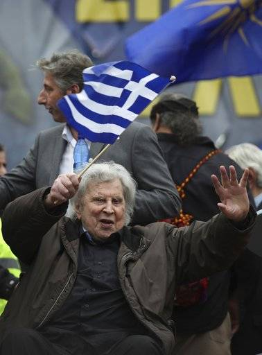 Famous Greek composer Mikis Theodorakis waves to the crowd after his speech at a rally in Athens, Sunday, Feb. 4, 2018. Protesters from across Greece converged Sunday on Athens' main square outside parliament to protest a potential Greek compromise in a dispute with neighboring Macedonia over the former Yugoslav republic's official name.