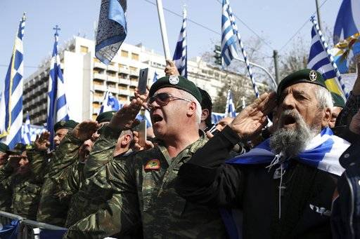 Greek army veterans salute as they sing the national anthem during a rally in Athens, Sunday, Feb. 4, 2018. Protesters from across Greece converged Sunday on Athens' main square outside parliament to protest a potential Greek compromise in a dispute with neighboring Macedonia over the former Yugoslav republic's official name.