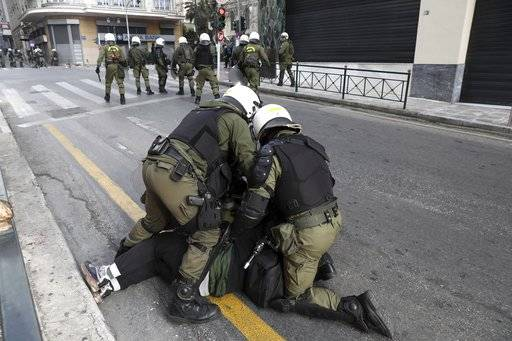 CORRECT NAME OF THE PHOTOGRAPHER Riot policemen detain a protester during a scuffle on the sidelines of a rally in Athens, Sunday, Feb. 4, 2018. Protesters from across Greece converged Sunday on Athens' main square outside parliament to protest a potential Greek compromise in a dispute with neighboring Macedonia over the former Yugoslav republic's official name.