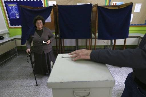 A woman votes during the presidential elections in southern coastal city of Limassol, Cyprus, on Sunday, Feb. 4, 2018. Cypriots are voting in the second round for a new president they hope will overcome years of failure to resolve the island-nation's ethnic division and deliver more benefits from an economy on the rebound after a severe financial crisis.