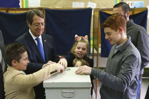 Cyprus' president Nicos Anastasiades and Cypriot Presidential candidate, escorted by his grandchildren votes during the presidential elections in southern coastal city of Limassol, Cyprus, on Sunday, Feb. 4, 2018. Cypriots are voting in the second round for a new president they hope will overcome years of failure to resolve the island-nation's ethnic division and deliver more benefits from an economy on the rebound after a severe financial crisis.