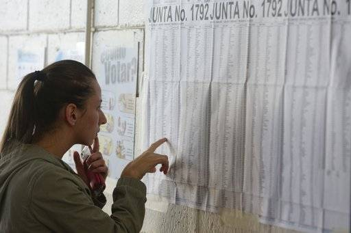 A woman scrolls the electoral list in search of her voting table location during the presidential election in San Jose, Costa Rica, Sunday, Feb. 4, 2018. Costa Ricans voted Sunday in a presidential race shaken by an international court ruling saying the country should let same-sex couples get married.