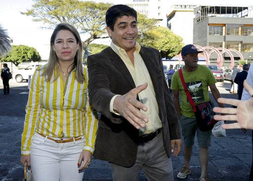 Presidential candidate Carlos Alvarado, right, with the Citizen Action party, greats a supporter as he arrives to a Mass at La Soledad church before casting his ballot during general elections in San Jose, Costa Rica, Sunday, Feb. 4, 2018. Costa Ricans voted Sunday in a presidential race shaken by an international court ruling saying the country should let same-sex couples get married.