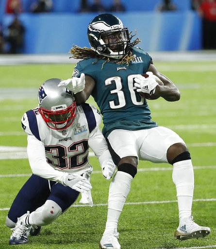 Philadelphia Eagles' Jay Ajayi, right, tries to get away from New England Patriots' Devin McCourty during the first half of the NFL Super Bowl 52 football game Sunday, Feb. 4, 2018, in Minneapolis.