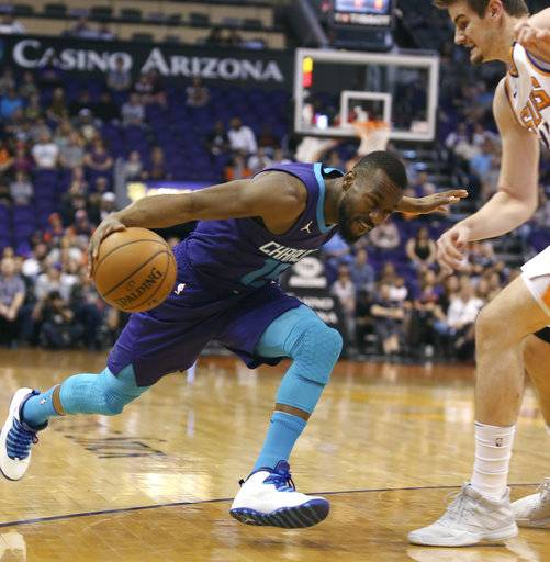 CORRECTS TO SUNDAY NOT SATURDAY - Charlotte Hornets guard Kemba Walker, left, drives to the basket as Phoenix Suns' Dragan Bender defends during the first half of an NBA basketball game Sunday, Feb. 4, 2018, in Phoenix.