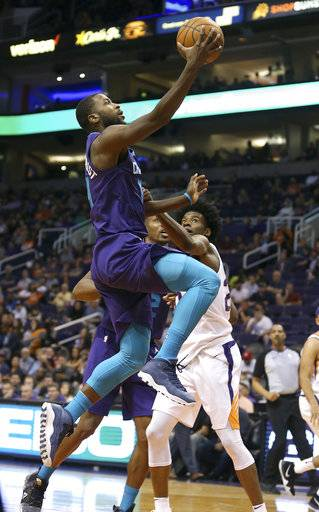 CORRECTS TO SUNDAY NOT SATURDAY - Charlotte Hornets guard Michael Kidd-Gilchrist, left, drives to the basket past Phoenix Suns' Josh Jackson during the first half of an NBA basketball game Sunday, Feb. 4, 2018, in Phoenix.