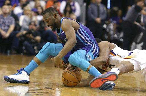 CORRECTS TO SUNDAY NOT SATURDAY - Charlotte Hornets guard Kemba Walker, left, and Phoenix Suns' T.J. Warren battle for the ball during the first half of an NBA basketball game Sunday, Feb. 4, 2018, in Phoenix.