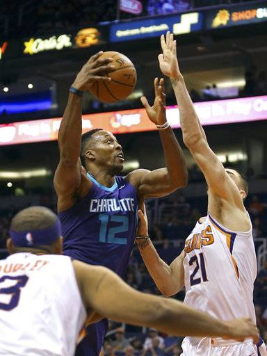 CORRECTS TO SUNDAY NOT SATURDAY - Charlotte Hornets center Dwight Howard (12) drives to the basket through the defense of Phoenix Suns' Alex Len (21) and Jared Dudley (8) during the first half of an NBA basketball game Sunday, Feb. 4, 2018, in Phoenix.