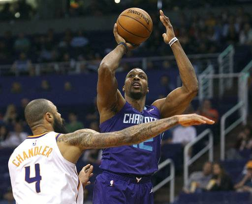 CORRECTS TO SUNDAY NOT SATURDAY - Charlotte Hornets center Dwight Howard, right, shoots over the defense of Phoenix Suns' Tyson Chandler during the first half of an NBA basketball game Sunday, Feb. 4, 2018, in Phoenix.