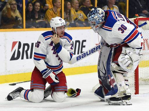 New York Rangers goaltender Henrik Lundqvist (30) checks on left wing Jimmy Vesey (26) who took a hard hit from a Nashville Predators player in the second period of an NHL hockey game Saturday, Feb. 3, 2018, in Nashville, Tenn. (George Walker IV/The Tennessean via AP)