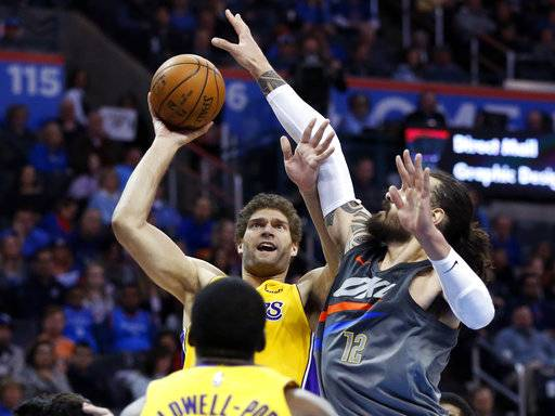 Los Angeles Lakers center Brook Lopez, top left, shoots in front of Oklahoma City Thunder center Steven Adams (12) in the first half of an NBA basketball game in Oklahoma City, Sunday, Feb. 4, 2018.