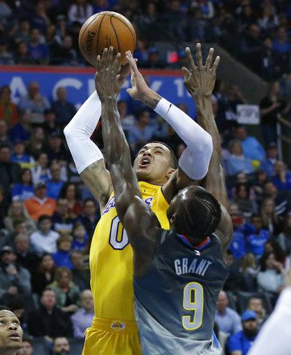 Los Angeles Lakers forward Kyle Kuzma (0) shoots as Oklahoma City Thunder forward Jerami Grant (9) defends in the first half of an NBA basketball game in Oklahoma City, Sunday, Feb. 4, 2018.
