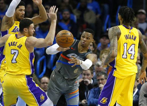Oklahoma City Thunder guard Russell Westbrook (0) passes between Los Angeles Lakers forwards Larry Nance Jr. (7) and Brandon Ingram (14) in the first half of an NBA basketball game in Oklahoma City, Sunday, Feb. 4, 2018.