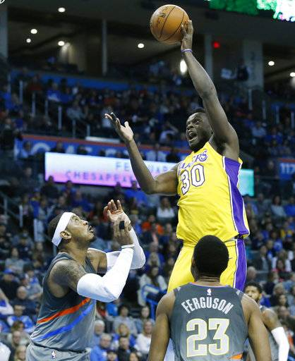 Los Angeles Lakers forward Julius Randle (30) shoots in front of Oklahoma City Thunder forward Carmelo Anthony, left, and guard Terrance Ferguson (23) in the first half of an NBA basketball game in Oklahoma City, Sunday, Feb. 4, 2018.