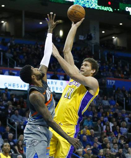 Los Angeles Lakers center Brook Lopez (11) shoots as Oklahoma City Thunder forward Paul George, left, defends in the first half of an NBA basketball game in Oklahoma City, Sunday, Feb. 4, 2018.