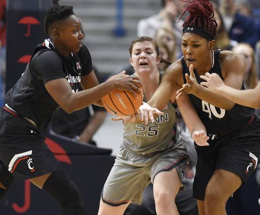 Connecticut's Kyla Irwin, center, cuts between a pass from Cincinnati's Shanice Johnson, left, to Cincinnati's Andeija Puckett, right, during the second half of an NCAA college basketball game, Sunday, Feb. 4, 2018, in Hartford, Conn.
