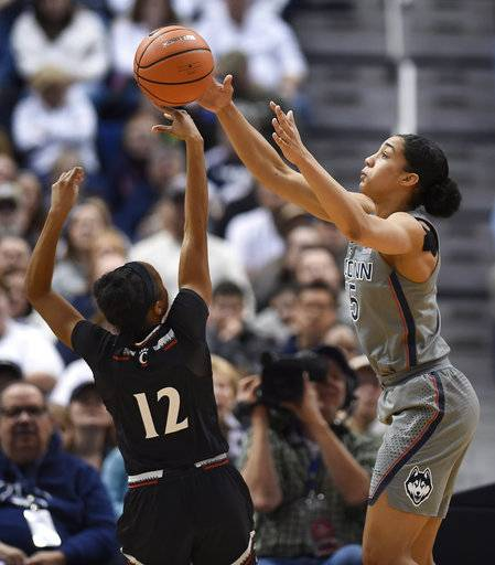 Connecticut's Gabby Williams, right, stops a shot-attempt and steals the ball from Cincinnati's Antoinette Miller, left, during the first half of an NCAA college basketball game, Sunday, Feb. 4, 2018, in Hartford, Conn.