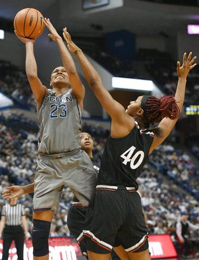 Connecticut's Azura Stevens, left, shoots as Cincinnati's Andeija Puckett, right, defends during the second half of an NCAA college basketball game, Sunday, Feb. 4, 2018, in Hartford, Conn.