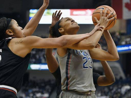 Cincinnati's Chelsea Warren, left, fouls Connecticut's Azura Stevens, right, during the first half of an NCAA college basketball game, Sunday, Feb. 4, 2018, in Hartford, Conn.