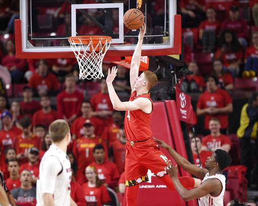 Maryland guard Kevin Huerter (4) goes to the basket against Wisconsin guard Khalil Iverson, bottom right, during the first half of an NCAA basketball game, Sunday, Feb. 4, 2018, in College Park, Md.