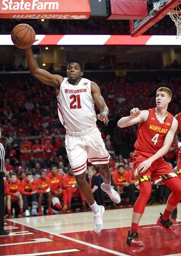 Wisconsin guard Khalil Iverson (21) reaches for the ball against Maryland guard Kevin Huerter (4) during the first half of an NCAA basketball game, Sunday, Feb. 4, 2018, in College Park, Md.