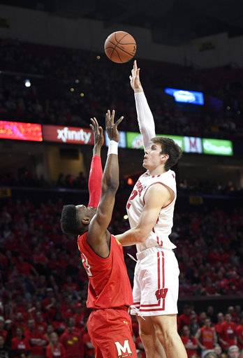 Wisconsin forward Ethan Happ, right, shoots against Maryland forward Bruno Fernando, left, during the first half of an NCAA basketball game, Sunday, Feb. 4, 2018, in College Park, Md.
