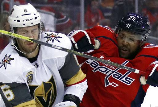 Vegas Golden Knights defenseman Colin Miller (6) takes a stick to the nose from Washington Capitals right wing Devante Smith-Pelly (25) in the second period of an NHL hockey game, Sunday, Feb. 4, 2018, in Washington.