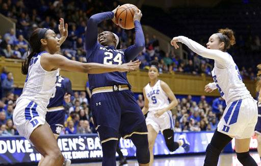 Notre Dame's Arike Ogunbowale (24) drives to the basket while Duke's Jayda Adams, right, and Lexie Brown defend during the first half of an NCAA college basketball game in Durham, N.C., Sunday, Feb. 4, 2018.