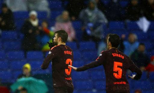 FC Barcelona's Gerard Pique, left, celebrates after scoring during the Spanish La Liga soccer match between Espanyol and FC Barcelona at RCDE stadium in Cornella Llobregat, Spain, Sunday, Feb. 4, 2018.