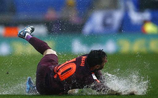 FC Barcelona's Lionel Messi falls during the Spanish La Liga soccer match between Espanyol and FC Barcelona at RCDE stadium in Cornella Llobregat, Spain, Sunday, Feb. 4, 2018.