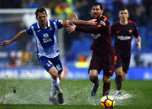 FC Barcelona's Lionel Messi, right, duels for the ball against Espanyol's Victor Sanchez during the Spanish La Liga soccer match between Espanyol and FC Barcelona at RCDE stadium in Cornella Llobregat, Spain, Sunday, Feb. 4, 2018.
