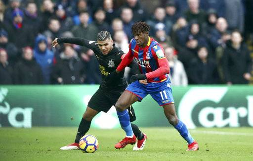 Crystal Palace's Wilfried Zaha, right, and Newcastle United's DeAndre Yedlin battle for the ball during the English Premier League soccer match at Selhurst Park, London, Sunday Feb. 4, 2018. (John Walton/PA via AP)