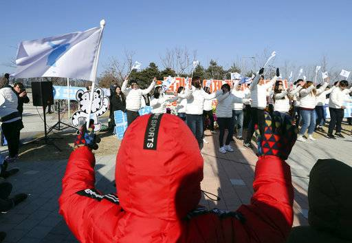 Supporters of combined Koreas women's ice hockey team wave the unification flags before the tune-up game between the combined Koreas team and Sweden prior to the 2018 Winter Olympics, outside of the ice rink in Incheon, South Korea, Sunday, Feb. 4, 2018.