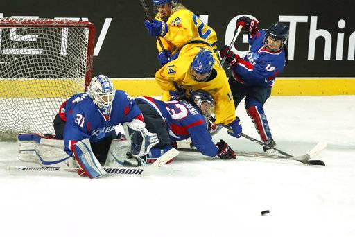 Combined Koreas' Park Yoon-jung, second from left, and Sweden's Sabina Kuller (14) battle for the puck during their women's ice hockey friendly game at Seonhak International Ice Rink in Incheon, South Korea, Sunday, Feb. 4, 2018. (Kim Hong-Ji/Pool Photo via AP)